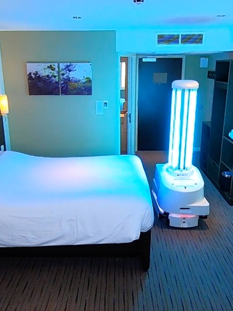 UVD Robot at the end of a bed showing how it can be used in the hospitality industry